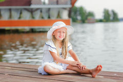 Beautiful girl in a hat sitting on a pier at the lake and looking into the distance on the water Royalty Free Stock Photo