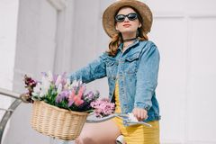 Beautiful girl in hat sunglasses and denim jacket riding bicycle. On street royalty free stock photography