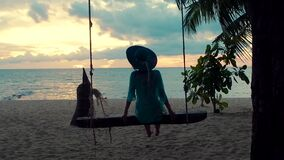Beautiful girl in a hat at sunset swinging on a swing on a seashore. Silhouette pretty young woman sitting on a hanging