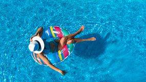 Beautiful girl in hat in swimming pool aerial top view from above, woman relaxes and swims on inflatable ring donut and has fun royalty free stock images