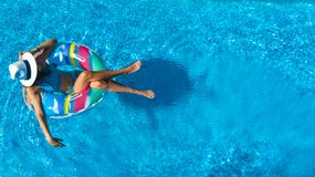 Beautiful girl in hat in swimming pool aerial top view from above, woman relaxes and swims on inflatable ring donut and has fun royalty free stock photography