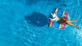 Beautiful girl in hat in swimming pool aerial top view from above, woman relaxes and swims on inflatable ring donut and has fun. In water on family vacation royalty free stock image