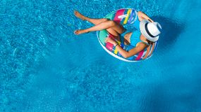 Beautiful girl in hat in swimming pool aerial top view from above, woman relaxes and swims on inflatable ring donut and has fun royalty free stock image