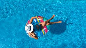 Beautiful girl in hat in swimming pool aerial top view from above, woman relaxes and swims on inflatable ring donut and has fun stock photo