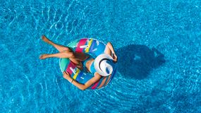 Beautiful girl in hat in swimming pool aerial top view from above, woman relaxes and swims on inflatable ring donut and has fun royalty free stock photo