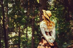 Beautiful girl in a hat in a vintage dress walking in a Summertime park. Forest. Lolita style stock image
