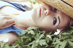 Beautiful girl in hat with white spring flowers Stock Images
