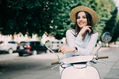 Beautiful girl in a hat in a white t-shirt and hat posing on a scooter Stock Image