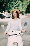 Beautiful girl in a hat in a white t-shirt and hat posing on a scooter Royalty Free Stock Image