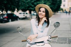 Beautiful girl in a hat in a white t-shirt and hat posing on a scooter Stock Images