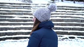 Beautiful girl in a hat and winter clothes smile while looks at camera and enjoys good weather. Positive emotion. Young. Woman in winter, snowy stairs stock video footage