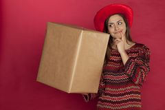 A beautiful girl in a hat wonders about a gift. On the red background Royalty Free Stock Image