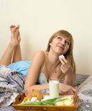 Beautiful girl having breakfast in bed royalty free stock images