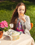 Beautiful girl having breakfast at yard and biting cookie Stock Photography