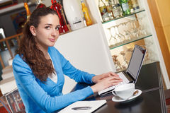 Beautiful girl having a coffee break and working on a computer Stock Image