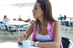 Beautiful girl having coffee on the street. Stock Photos