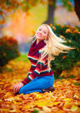 Beautiful girl having fun in autumn park among vibrant leaves Stock Image