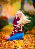 Beautiful girl having fun in autumn park among vibrant leaves Stock Image