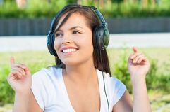 Beautiful girl having fun in park listening to music Stock Photos