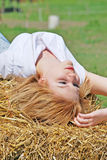 Beautiful girl on a hay bale Stock Photography