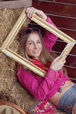 Beautiful girl in hay with a frame Stock Image
