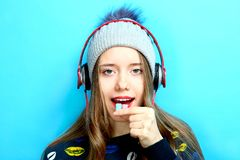 Girl in headphones with chewing gum. Beautiful girl in headphones with chewing gum on a blue background royalty free stock images