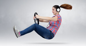 Beautiful girl in headphones driver car with a wheel. Auto concept stock image