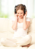 Beautiful girl in headphones enjoying music at home Stock Images