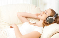 Beautiful girl in headphones enjoying music at home Stock Image