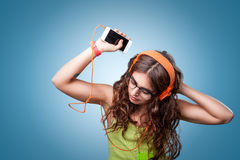 Beautiful girl in headphones listening to music and dancing Stock Photography
