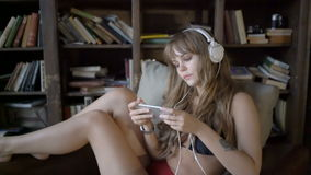 Beautiful girl in headphones is listening to music using a smartphone at home. Young girl in headphones is listening to music using a smartphone at home stock video footage