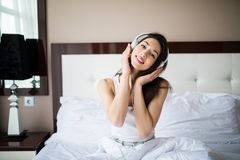 Beautiful girl in headphones is listening to music using a smartphone, looking at camera and smiling while lying on bed at home Royalty Free Stock Images