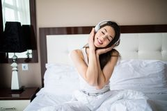 Beautiful girl in headphones is listening to music using a smartphone, looking at camera and smiling while lying on bed at home Royalty Free Stock Photography
