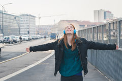 Beautiful girl with headphones posing in the city streets Stock Photography