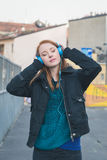 Beautiful girl with headphones posing in the city streets Stock Images