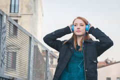 Beautiful girl with headphones posing in the city streets Stock Image