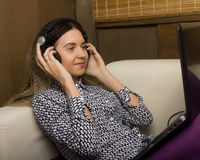 Beautiful girl in headphones sitting on a couch on her knees laptop Royalty Free Stock Images