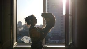 Beautiful girl in headphones, talking with a fluffy cat on her hands, against the background of an open window stock video footage
