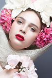 Beautiful girl in a headscarf in the Russian style, with large flowers on his head and red lips. Beauty face. Royalty Free Stock Images