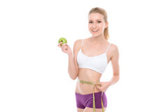 Beautiful girl and healthy food. Portrait of a beautiful young blond fit girl wearing white bra and violet panties standing smiling and holding a green apple and Stock Images