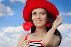 Beautiful Girl with Heart Lollipop and Straw Hat on Blue Sky Stock Images