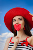 Beautiful Girl with Heart Lollipop and Straw Hat on Blue Sky Royalty Free Stock Image