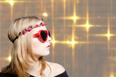 Beautiful girl in heart shaped sunglasses on bokeh Stock Photography