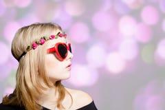 Beautiful girl in heart shaped sunglasses on bokeh Stock Photos
