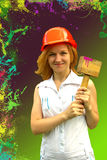 Beautiful girl in a helmet with construction hammer on a green and burgundy background with splashes of paint Stock Photos