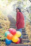 Beautiful girl with her balloons. Climbing stairs stock images