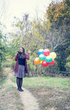 Beautiful girl with her balloons and guitar. In autumn Royalty Free Stock Photo
