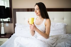 Beautiful girl at her bedroom drinking tea in the morning. Royalty Free Stock Images