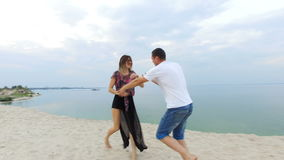 Beautiful girl and her boyfriend playing on the seashore - the guy doganyaet girl and kisses her.  stock video