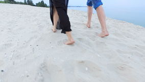 Beautiful girl and her boyfriend walking along the seashore - the feet are in the sand.  stock video footage